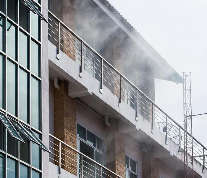 A commercial building with smoke coming out the windows.
