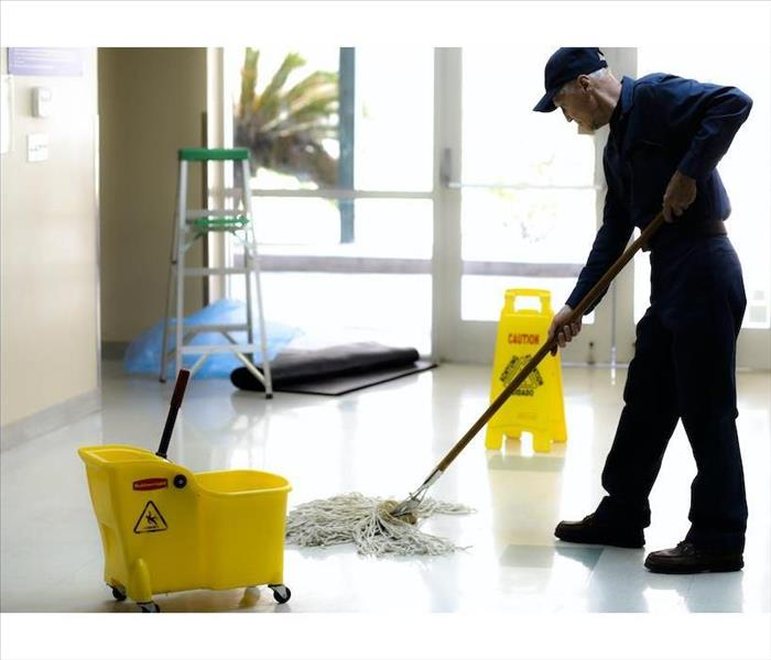 male mopping a white floor with a yellow bucket and sign